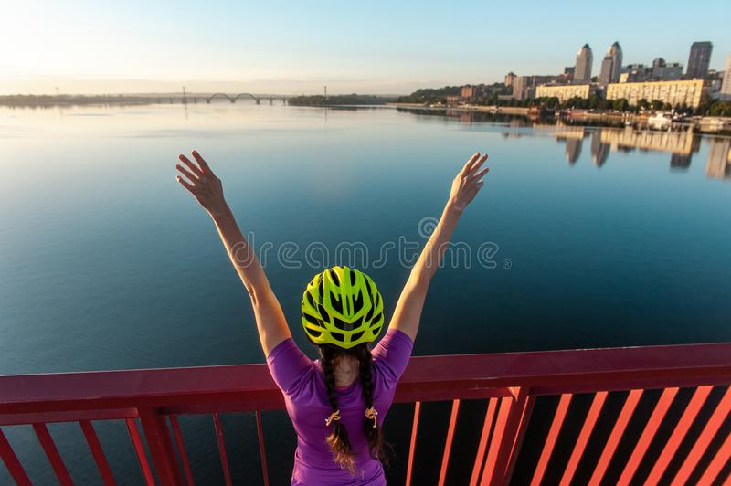 Girl cyclist  with a raised hands in the sunset stock images