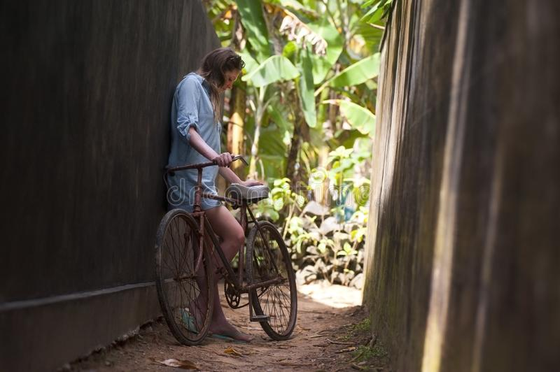 Girl with bicycle on narrow alley royalty free stock photo