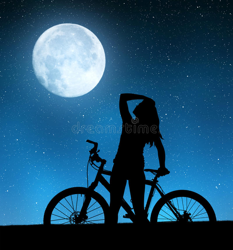 Girl on a bicycle. In night sky stock photos