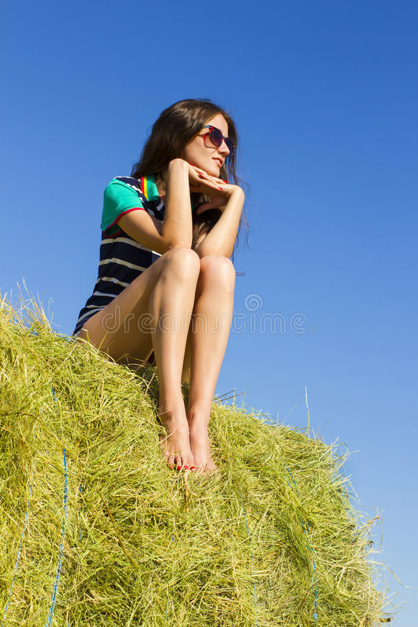 Girl on the big haystack. Pretty lady is sitting on the big haystack and looking into the distance royalty free stock photos