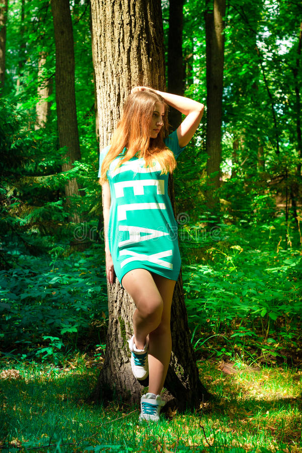 The girl and the big tree in the forest royalty free stock images