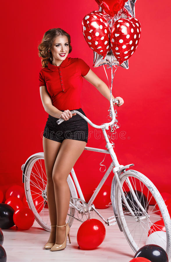 Girl with bike and balloons royalty free stock photo