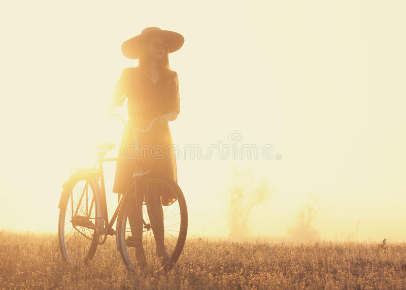 Girl on a bike. In the countryside in sunrise time stock images