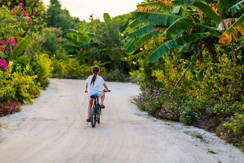 Girl on bike ride. Cute girl biking at tropical island settings having fun stock photos