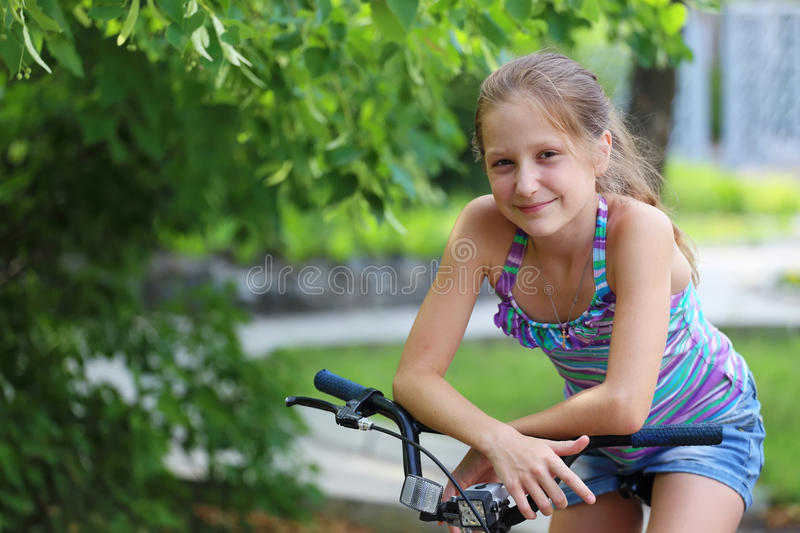 Girl with bike. Smiling little girl sitting on a bike stock photos