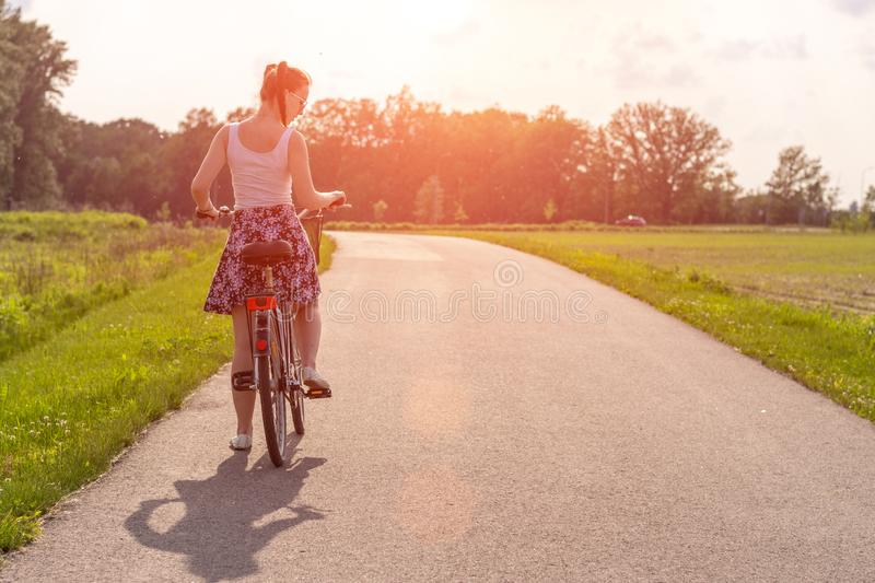 Girl with bike at the summer sunset on the road in the city park. Cycle closeup wheel on blurred summer background. Cycling down t stock photography