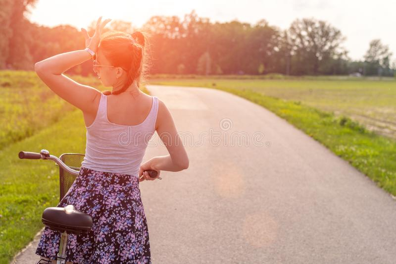 Girl with bike at the summer sunset on the road in the city park. Cycle closeup wheel on blurred summer background. Cycling down t stock image