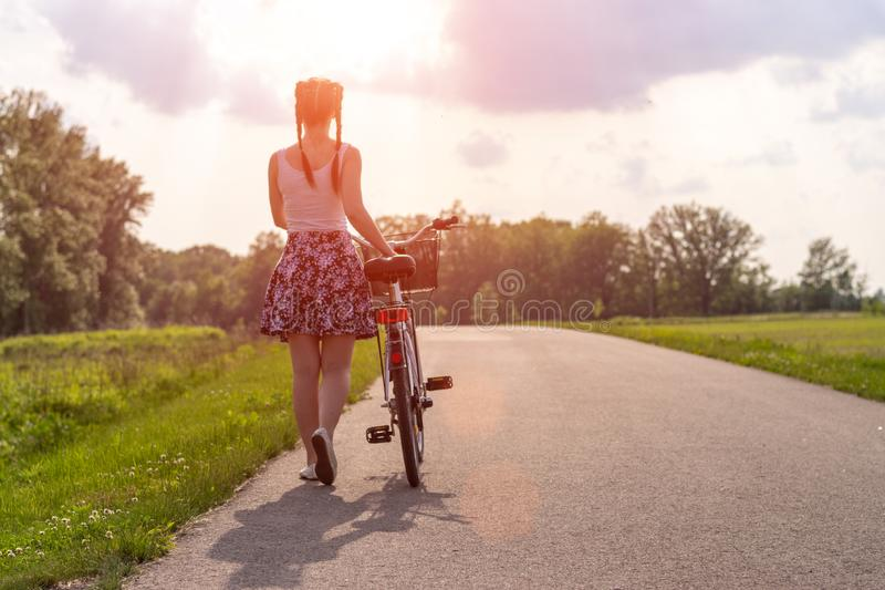 Girl with bike at the summer sunset on the road in the city park. Cycle closeup wheel on blurred summer background. Cycling down t stock photo