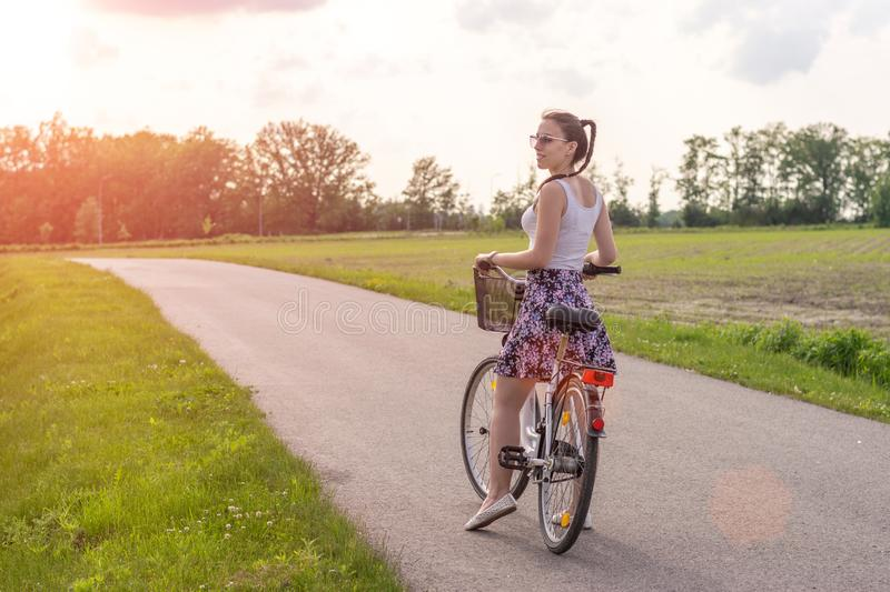 Girl with bike at the summer sunset on the road in the city park. Cycle closeup wheel on blurred summer background. Cycling down t royalty free stock images