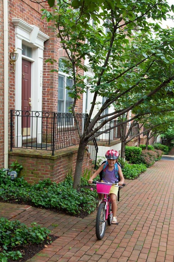 Girl Biking to School. May 9, 2012 - Arlington, Virginia, USA - National Bike to School Day, Key School Escuela Key Elementary stock photography