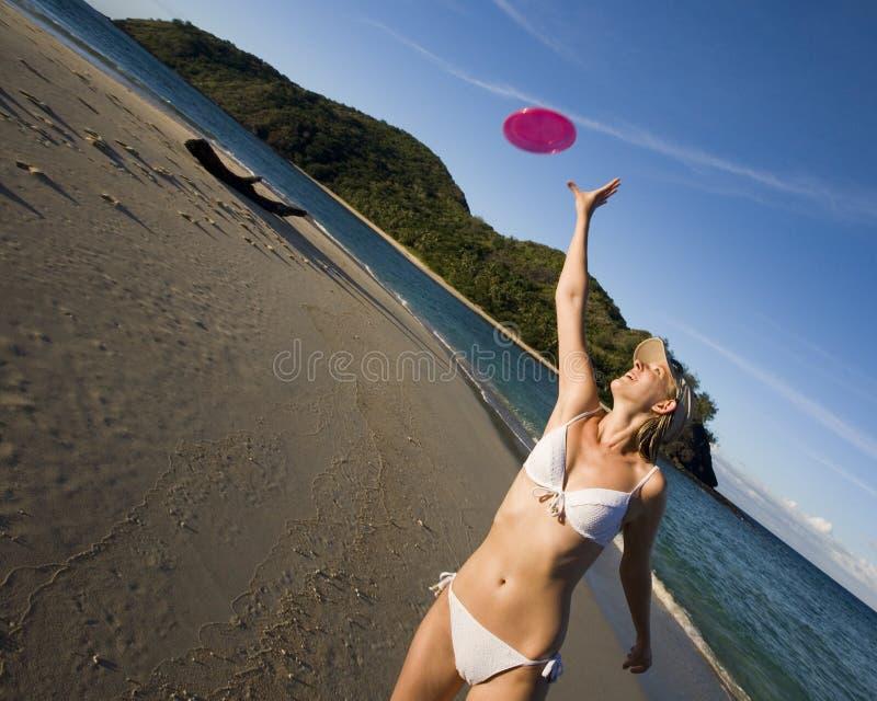 Girl in bikini catching a frisbee - tropical beach stock image