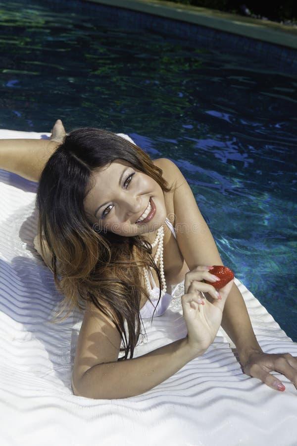 Girl in bikini on a raft in a pool royalty free stock image