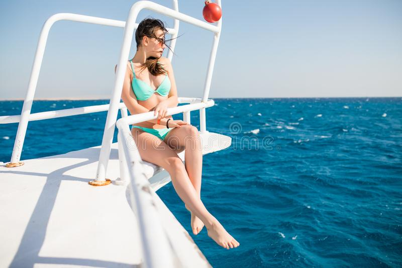Girl in a bikini rest on a deck of yacht in the middle of the ocean. Beautiful girl at the resort. Weekend on a yacht. Cruise on a royalty free stock photos