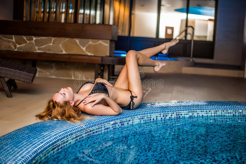 Girl in bikini sits at hotel spa zone royalty free stock photo