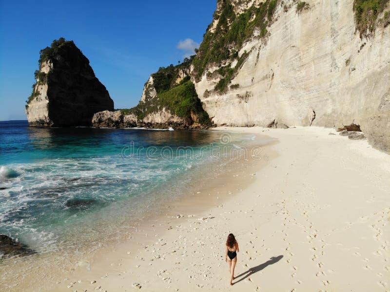 Girl in bikini walking on beach near ocean. Vacation in Nusa Penida. Photo from drone stock photos