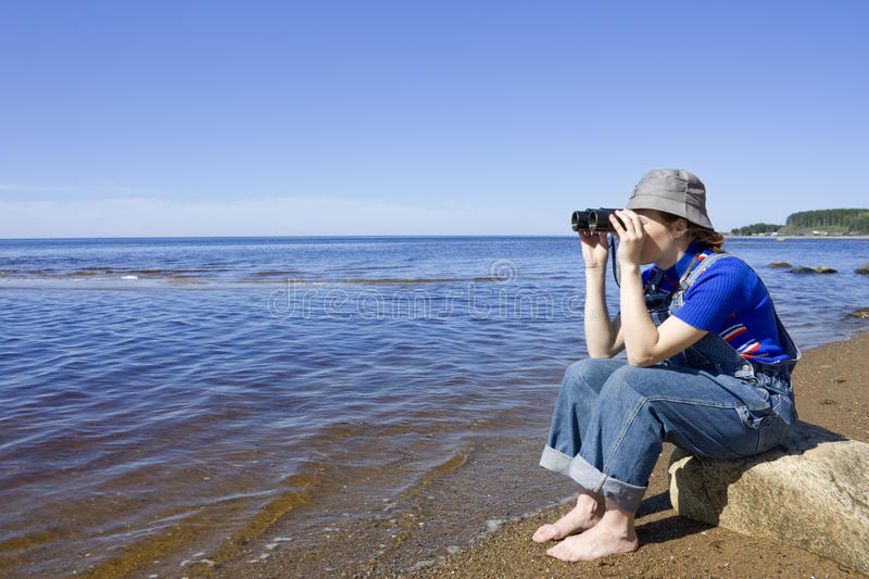 The girl with the binoculars. Woman with binoculars looking out to sea royalty free stock photography