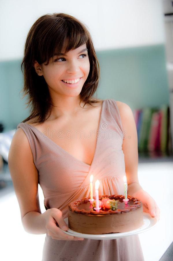 Girl With Birthday Cake. A young attractive woman holding a birthday cake with lit candles stock images