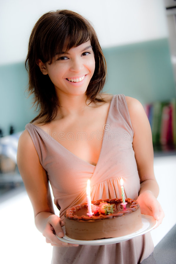 Girl With Birthday Cake. A young attractive woman holding a birthday cake with lit candles royalty free stock photography