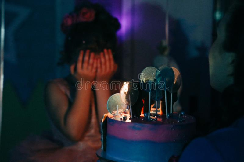 Girl with birthday cake closed her eyes with her hands making a wish in dark room, burned candles royalty free stock images