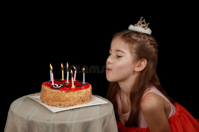 Girl with birthday cake. Princess anniversary - cute girl in red dress and crown on head going to blow out the candles on birthday cake - low key side view on stock photo