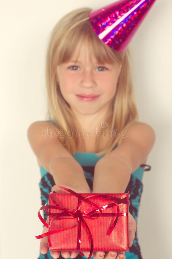 Girl with a birthday gift and cap. Girl 5 years with a birthday gift and cap royalty free stock photography