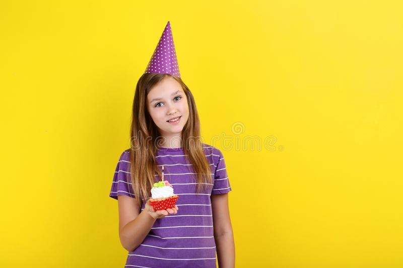 Girl in birthday hat holding cupcake. Young girl in birthday hat holding cupcake with candle on yellow background royalty free stock photography