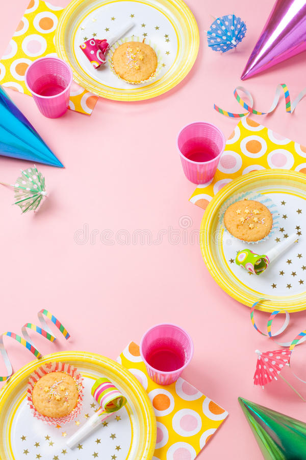 Girl birthday or party pink table setting. Girl birthday pink table setting from above with muffins, drinks and party gadgets. Background layout with free text royalty free stock image