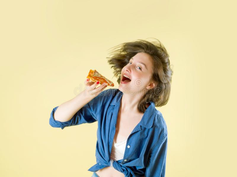 Girl bites a slice of pizza on a yellow background. Girl and Pizza royalty free stock photography