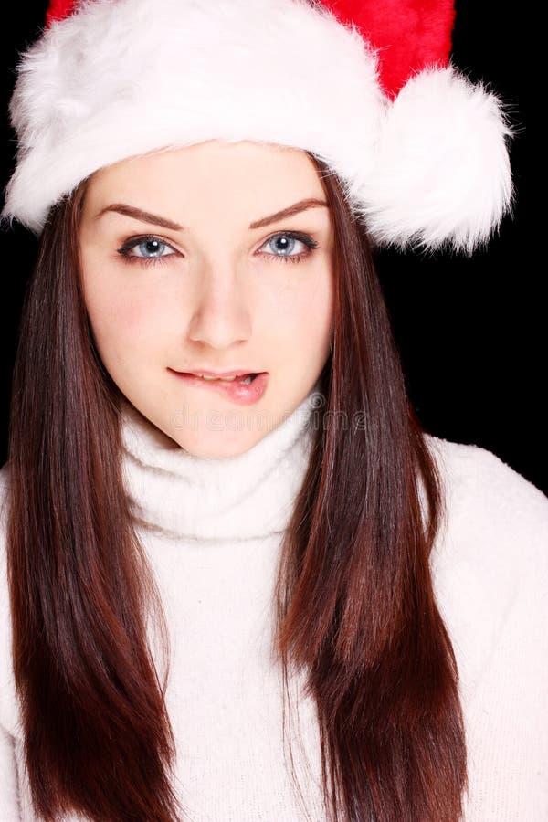 Girl biting her lip wearing Santa hat royalty free stock photos