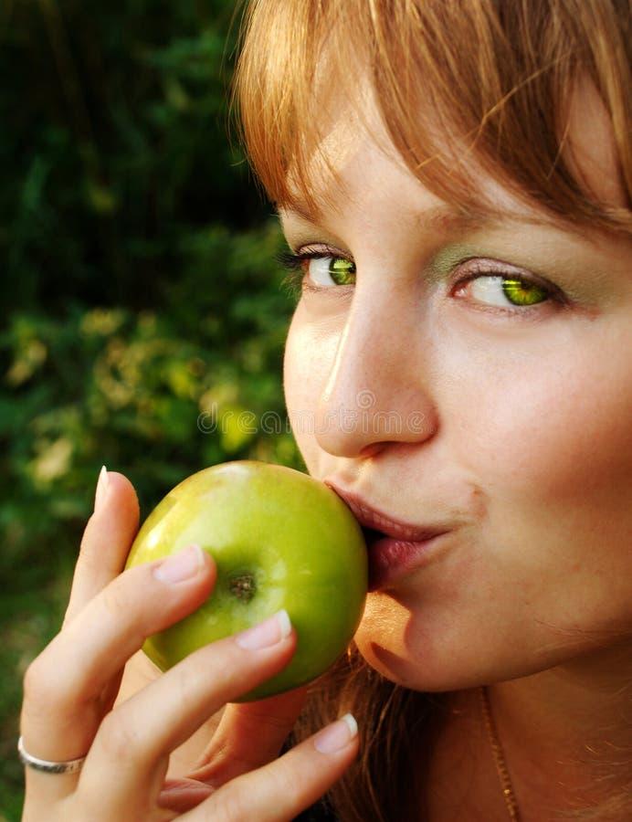 Girl bitten apple stock photo