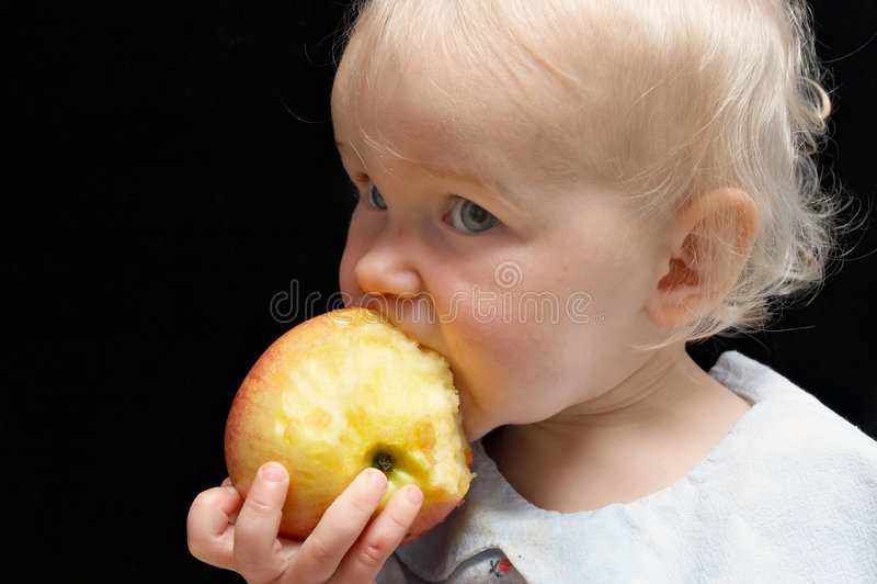 Girl bitting apple royalty free stock photo