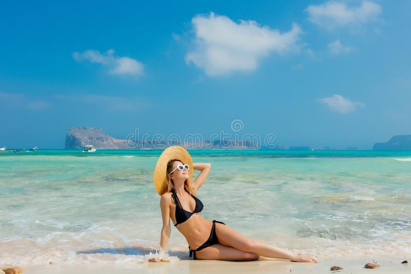 Girl in black bikini and with hat on Balos beach. Young redhead girl in black bikini and with hat on Balos beach, west Crete, Greece. Summertime season vacation royalty free stock photos
