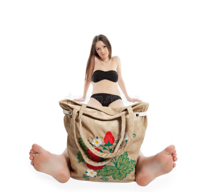 Girl in black bikini sit with funny beach bag stock images
