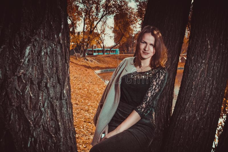 Beautiful happy woman walking in the autumn city park among the trees. there is orange leaves and foliage on the ground. Portrait royalty free stock photo