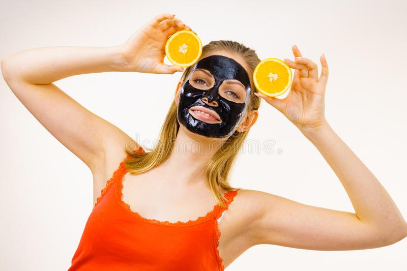 Girl black carbo mask on face holds orange fruit. Woman with carbo detox black peel-off mask on face holding orange fruit. Teen girl taking care of oily skin royalty free stock photography