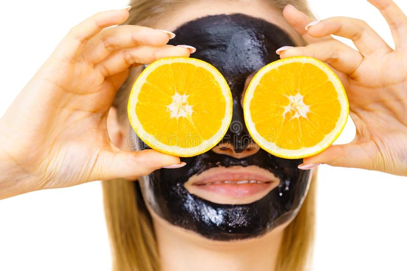 Girl black carbo mask on face holds orange fruit. Woman with carbo detox black peel-off mask on face holding orange fruit. Teen girl taking care of oily skin stock photography
