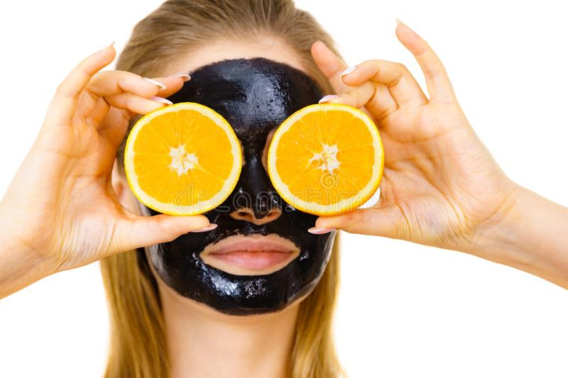 Girl black carbo mask on face holds orange fruit. Woman with carbo detox black peel-off mask on face holding orange fruit. Teen girl taking care of oily skin royalty free stock photos