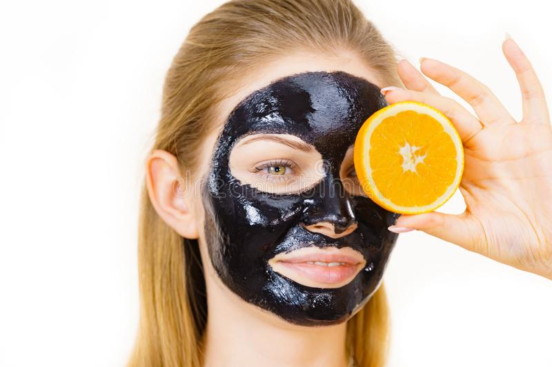 Girl black carbo mask on face holds orange fruit. Woman with carbo detox black peel-off mask on face holding orange fruit. Teen girl taking care of oily skin stock images