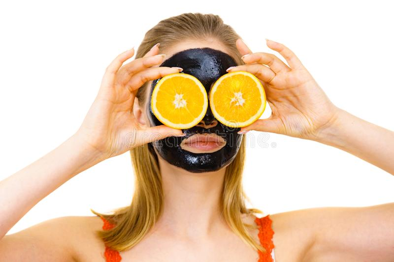 Girl black carbo mask on face holds orange fruit. Woman with carbo detox black peel-off mask on face holding orange fruit. Teen girl taking care of oily skin royalty free stock images