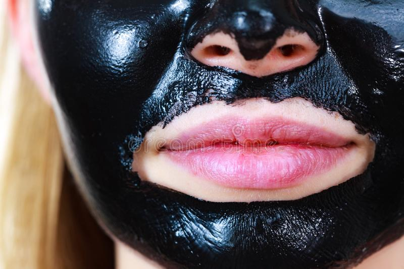 Girl black carbo peel off mask on face. Close up woman with carbo detox black peel-off mask on her face, detail view. Teen girl taking care of oily skin royalty free stock image