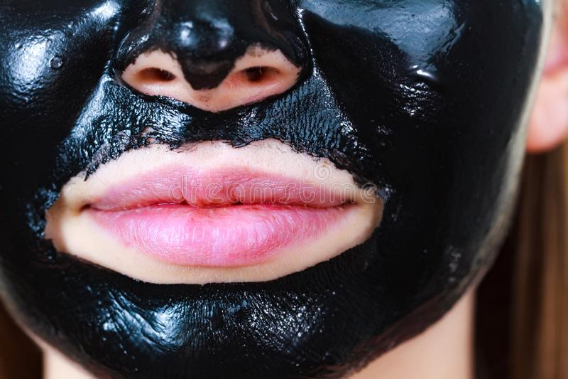 Girl black carbo peel off mask on face. Close up woman with carbo detox black peel-off mask on her face, detail view. Teen girl taking care of oily skin royalty free stock images