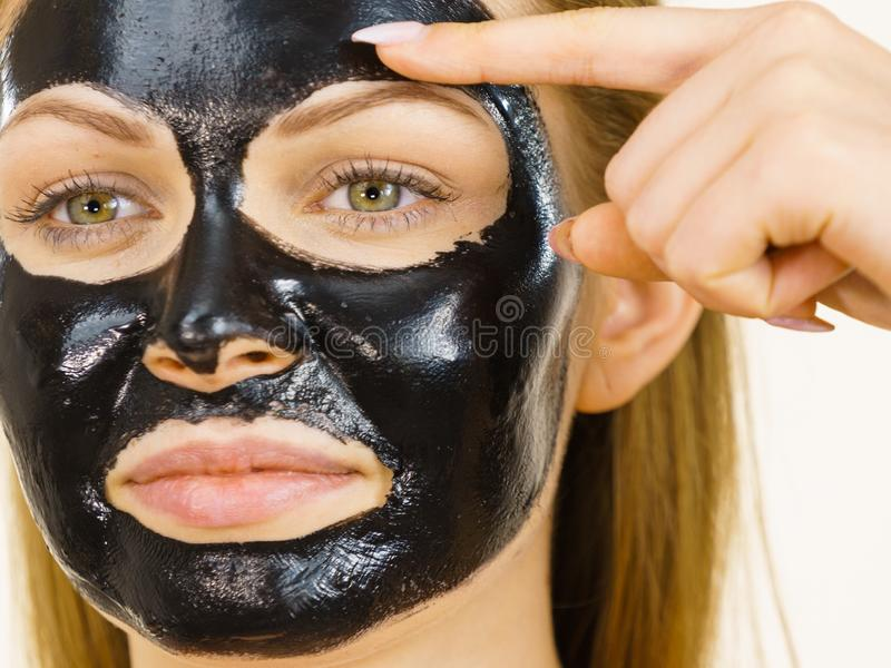 Girl black carbo peel off mask on face. Young woman with carbo detox black peel-off mask on her face, on white. Teen girl taking care of oily skin, cleaning the stock images