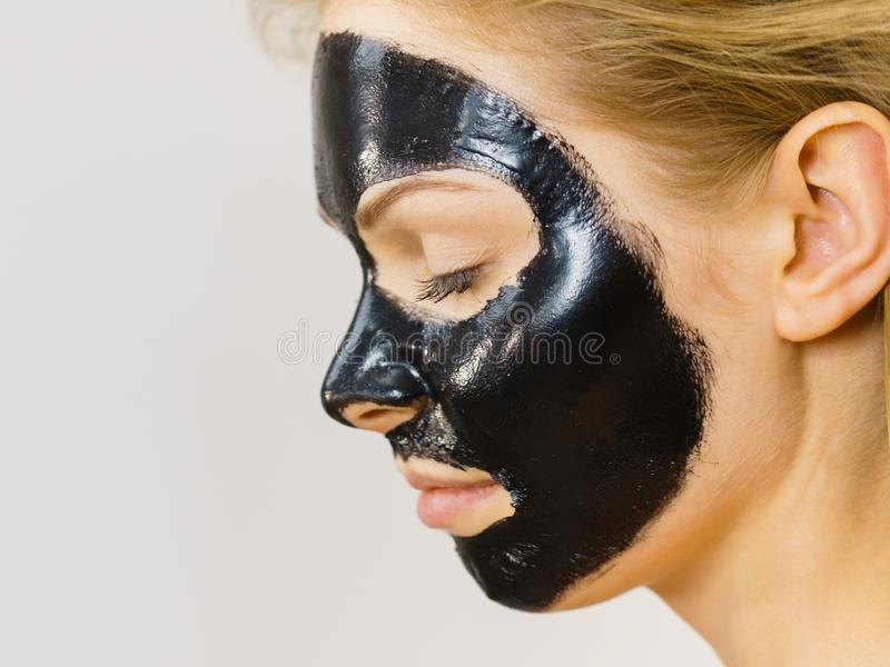 Girl black carbo peel off mask on face. Young woman with carbo detox black peel-off mask on her face, on white. Teen girl taking care of oily skin, cleaning the stock image