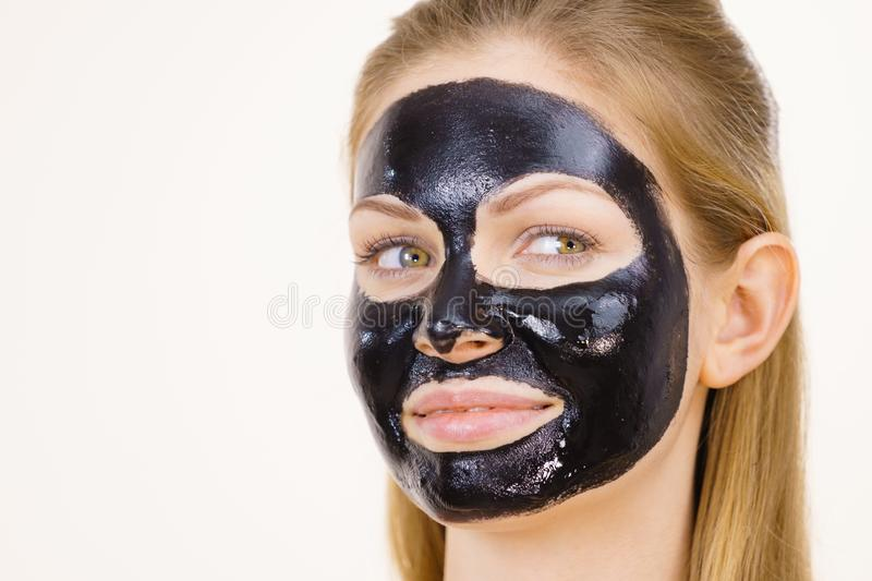 Girl black carbo peel off mask on face. Young woman with carbo detox black peel-off mask on her face, on white. Teen girl taking care of oily skin, cleaning the stock photography