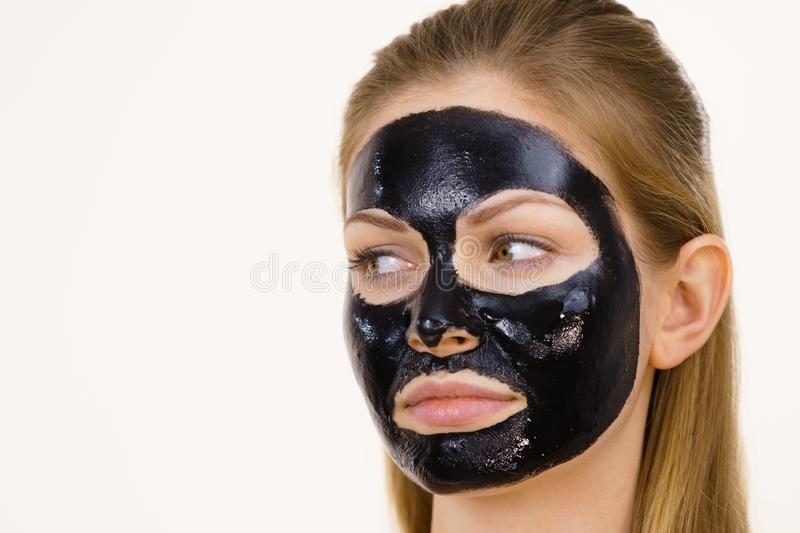 Girl black carbo peel off mask on face. Young woman with carbo detox black peel-off mask on her face, on white. Teen girl taking care of oily skin, cleaning the royalty free stock photos