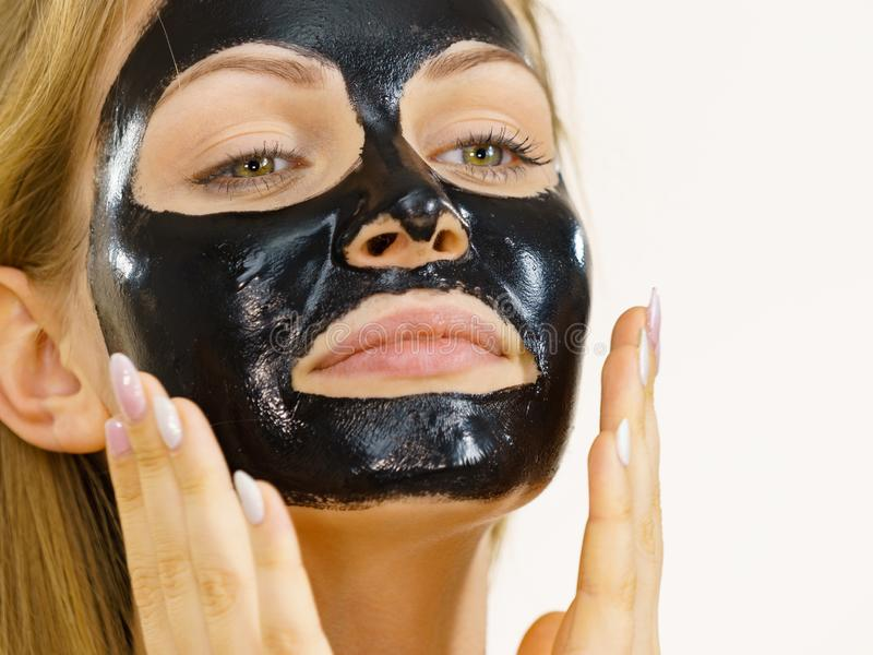 Girl black carbo peel off mask on face. Young woman with carbo detox black peel-off mask on her face, on white. Teen girl taking care of oily skin, cleaning the royalty free stock images