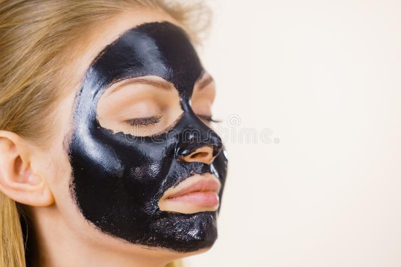 Girl black carbo peel off mask on face. Young woman with carbo detox black peel-off mask on her face, on white. Teen girl taking care of oily skin, cleaning the royalty free stock image