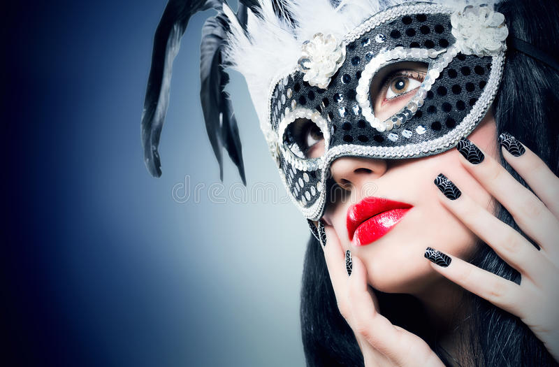 Girl in black carnival mask with manicure. Beautiful young woman in black carnival mask with manicure royalty free stock image