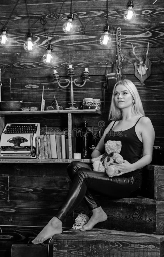 Girl in black clothes holds teddy bear toy in hand, wooden interior on background. Woman on dreamy face relaxing in. Wooden interior. Lady blonde enjoy leisure stock photography