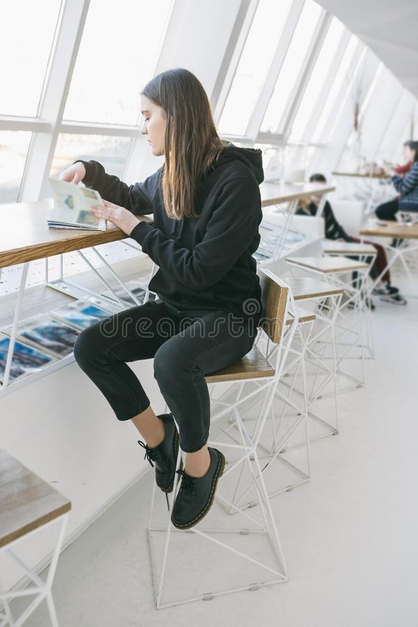 Girl in black clothes sitting on a high bar stool in a cafe and reading magazine. light interior. Relaxed mood stock photography